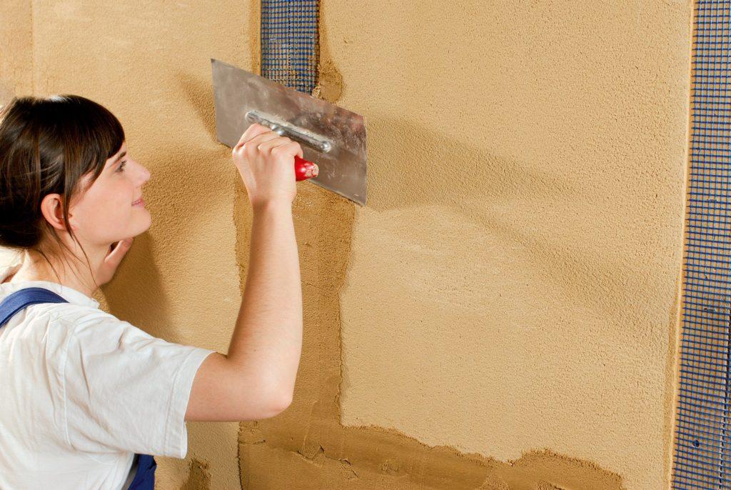 Eine junge Frau verputzt die Wand mit BKM Spachtel.